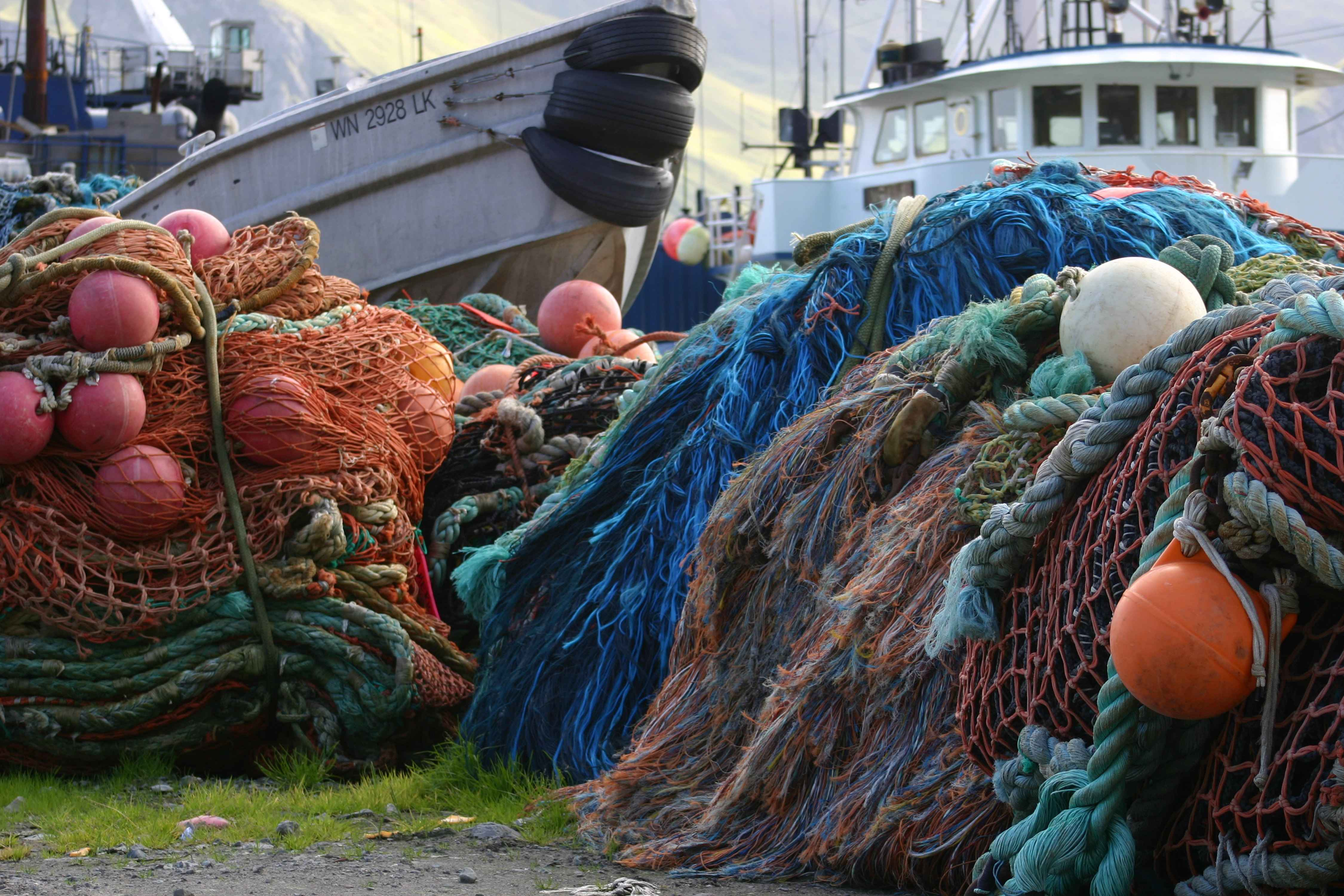 by Stanley Carla US Fish and WIldlife Service Fish net pile in harbor with ships
